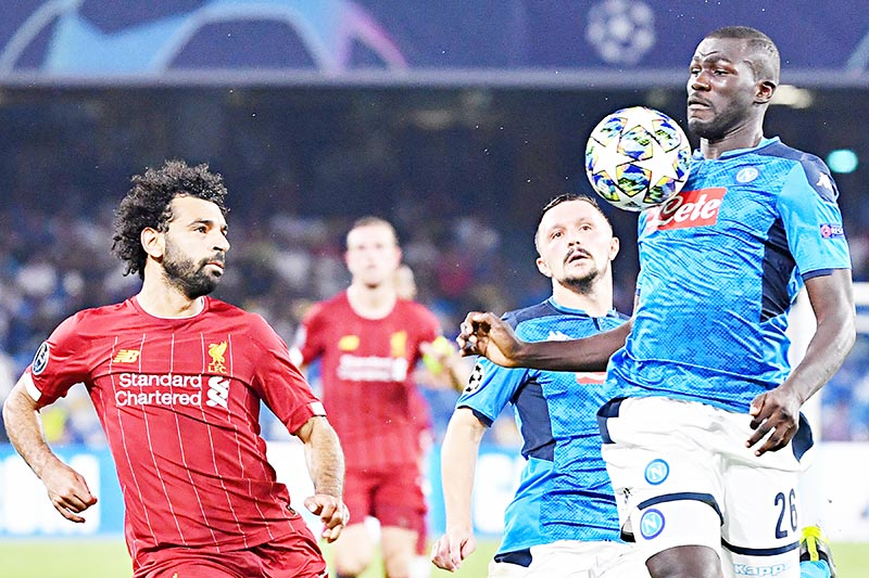Napoli's Senegalese defender Kalidou Koulibaly (R) chest controls the ball under pressure from Liverpool's Egyptian midfielder Mohamed Salah (L) as Napoli's Portuguese defender Mario Rui looks on during the UEFA Champions League Group E football match Napoli vs Liverpool on September 17, 2019 at the San Paolo stadium in Naples.	photo: AFP