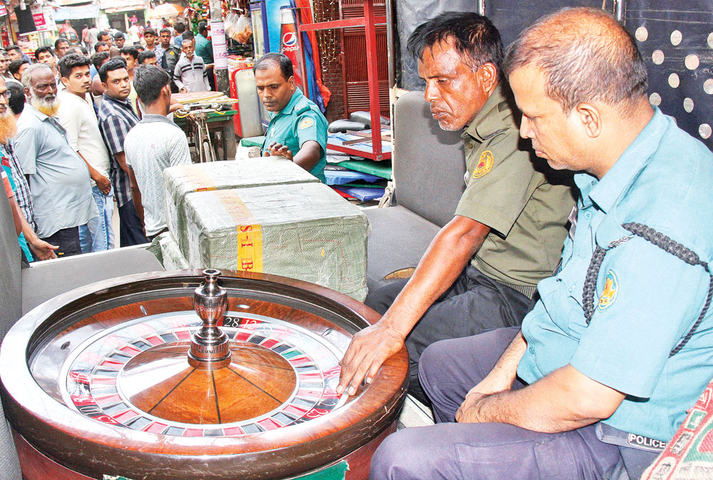 Police conducting a raid on the Dilkusha Sporting Club in the capital's Motijheel on Sunday. Cops seized gambling boards, shisha bar, a huge number of playing cards, teller machines and cash taka one lakh from the club.photo : Observer
