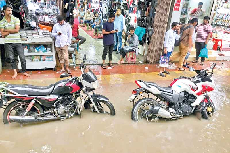 A heavy rainfall inundates many areas of the capital in knee-deep water on Sunday, causing immense suffering to the city dwellers. The photo was taken from Elephant Road.	PHOTO: OBSERVER