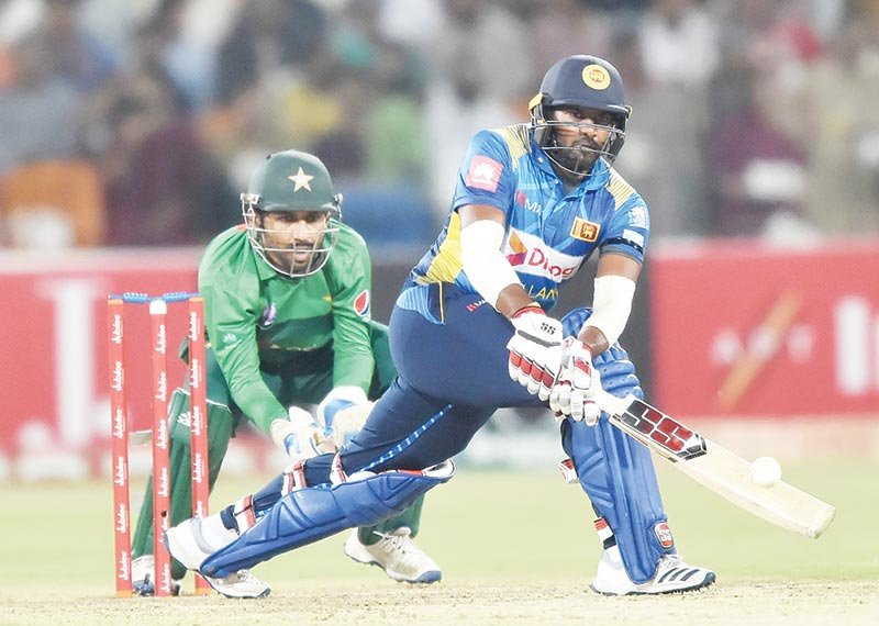 Sri Lanka's Bhanuka Rajapaksa (R) plays a shot as Pakistan's captain and wicketkeeper Sarfraz Ahmed looks on during the second Twenty20 International cricket match between Pakistan and Sri Lanka at the Gaddafi Cricket Stadium in Lahore on October 7, 2019.	photo: AFP