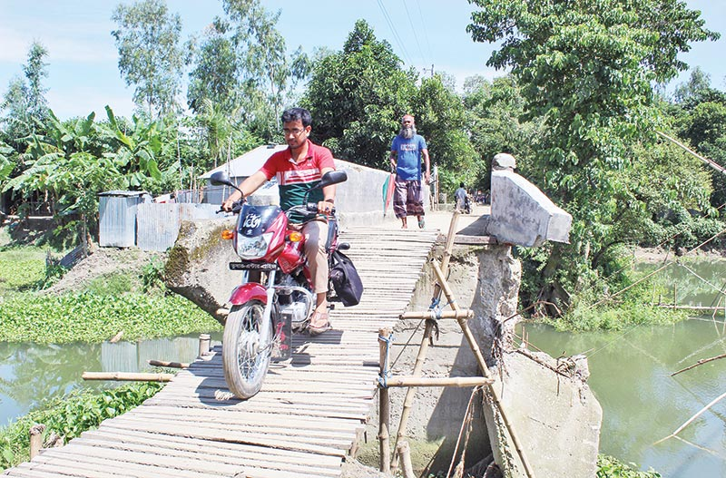 Sonatala people cross bridge amid risk