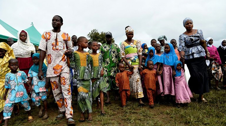 Parents lead children at a parade of twins at the Igbo-Ora festival. The one-day event draws families from across Nigeria