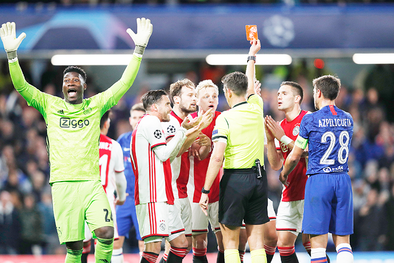 Ajax's players react after Ajax's Dutch defender Joel Veltman (hidden) is shown a red card by Italian referee Gianluca Rocchi during the UEFA Champion's League Group H football match between Chelsea and Ajax at Stamford Bridge in London on November 5, 2019.	photo: AFP
