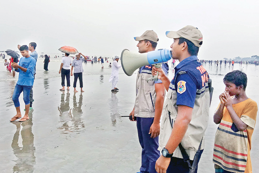 Security members of Kuakata Beach in Patuakhalo on Friday warning people using bullhorn to take refuge at cyclone shelters amid the Danger Signal No 7 as cyclonic storm 'Bulbul' approaching. 	PHOTO: OBSERVER