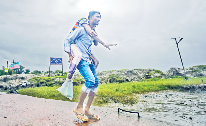 A man carries another person on his back to a cyclone shelter at Mongla of Khulna district. The picture was taken on Saturday.	PHOTO: OBSERVER