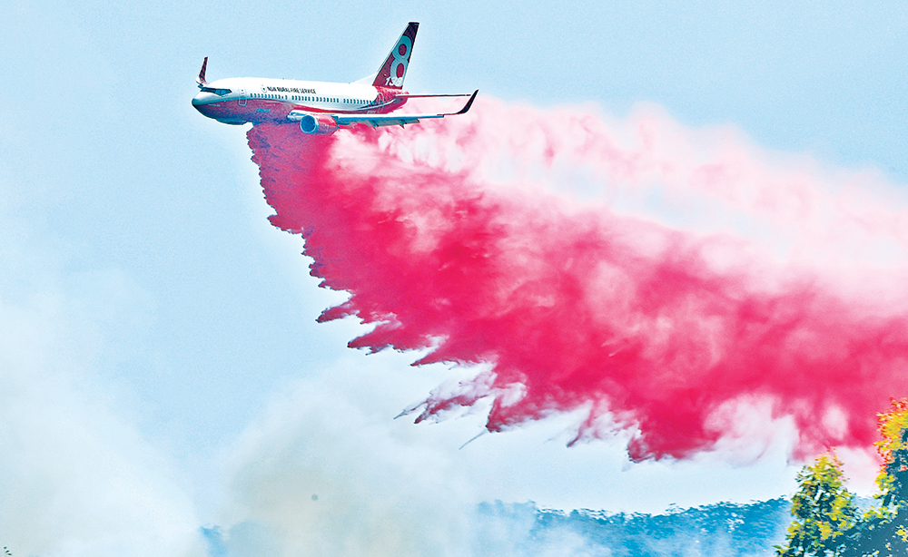 """A Rural NSW Fire Service plane drops fire retardant on an out of control bushfire near Taree, 350km north of Sydney on November 12. A state of emergency was declared and residents in the Sydney area were warned of """"catastrophic"""" fire danger.photo : AFP"""
