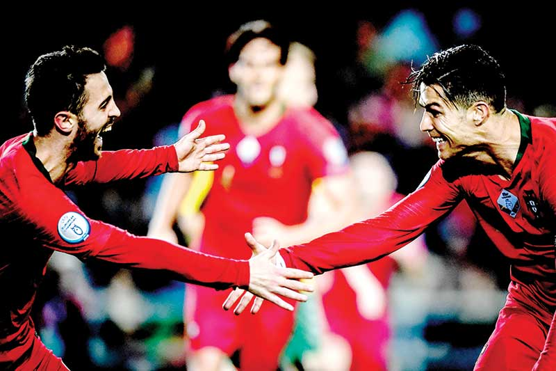 Portugal's forward Cristiano Ronaldo (R) celebrates with his teammate Portugal's forward Bernardo Silva (L) after scoring during the Euro 2020 Group B football qualification match between Portugal and Lithuania at the Algarve stadium in Faro, on November 14, 2019. photo: AFP