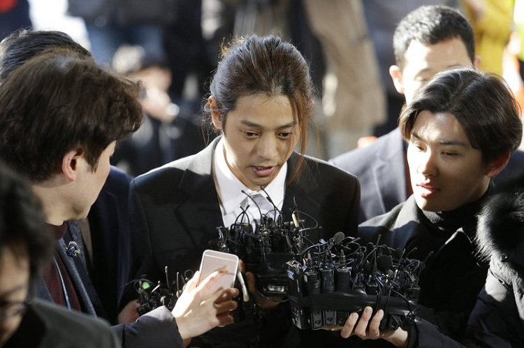 FILE - In this March 14, 2019, file photo, K-pop singer Jung Joon-young, center, speaks upon his arrival at the Seoul Metropolitan Police Agency in Seoul, South Korea. A South Korean court has found two K-pop stars guilty of illicit sexual relations with a woman who was unable to resist and sentenced them to up to six years in prison. The Seoul Central District Court says singer-songwriter Jung received a six-year prison term --AP Photo/Ahn Young-joon