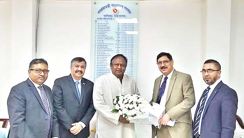Commerce Minister Tipu Munshi (middle) receives a bouquet from American Chamber of Commerce