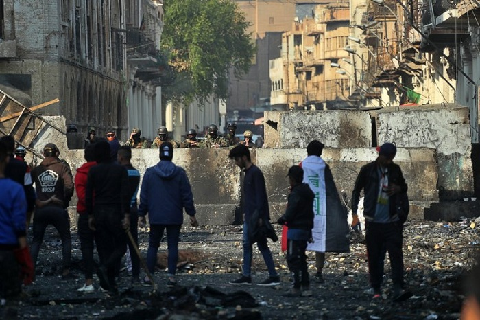 Anti-government protesters gather near barriers set up by security forces to close Rasheed Street during ongoing protests in Baghdad, Iraq, Thursday, Dec. 5, 2019  --AP Photo/Khalid Mohammed