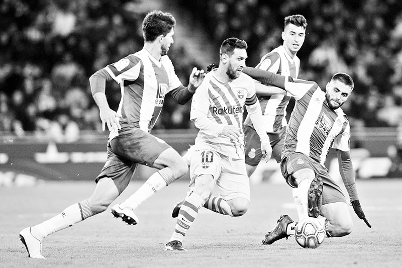 Barcelona's Argentine forward Lionel Messi (C) vies with Espanyol's Spanish defender Didac Vila (L) and Espanyol's Spanish midfielder David Lopez (R) during the Spanish league football match between RCD Espanyol and FC Barcelona at the RCDE Stadium in Cornella de Llobregat on January 4, 2020.	photo: AFP