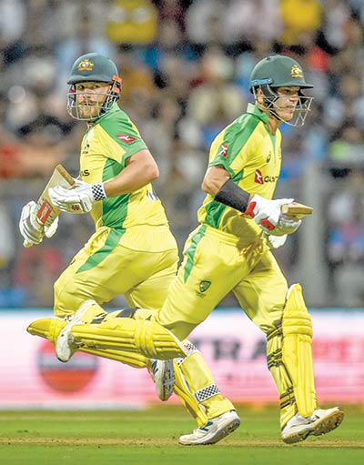 Australia's Aaron Finch (L) and David Warner run between the wickets during the first one day international (ODI) cricket match of a three-match series between India and Australia at the Wankhede Stadium in Mumbai on January 14, 2020.photo: AFP
