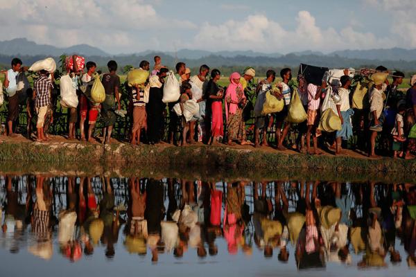 Rohingya refugees who fled from Myanmar wait to be let through by Bangladeshi border guards after crossing the border in Palang Khali, Bangladesh October 9, 2017.Photo: Reuters