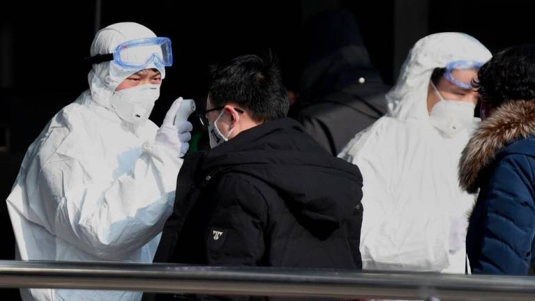 Travellers are checked by security personnel wearing hazardous material suits at the entrance to the underground train station in Beijing on Jan 24, to help stop the spread of a deadly SARS-like virus which originated in the central city of Wuhan. — AFP