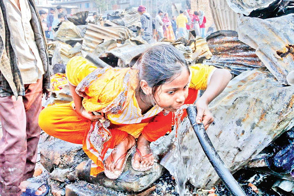 A girl of the slum drinks water from a singed water pipe.	photo : Observer