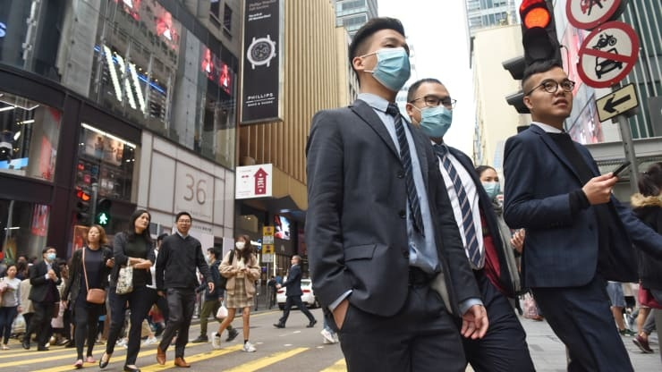 Pedestrians cover their faces with sanitary masks after the first cases of coronavirus have been confirmed in Hong Kong, China on January 23, 2020. --Miguel Candela Poblacion | Anadolu Agency | Getty Images