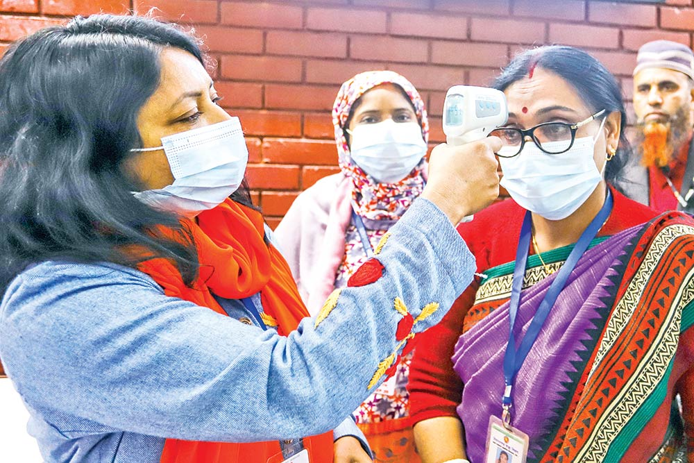 A medical official takes the body temperature of a woman at the departure hall of the Hazrat Shahjalal International Airport in Dhaka on Monday amid coronavirus outbreak in China.PHOTO: OBSERVER