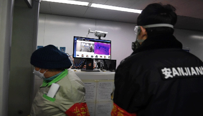 A security guard keeps watch as an AI-powered system developed by Chinese tech firm Megvii screens commuters for fevers as they enter the Mudanyuan metro station in Beijing on February 6, 2020. photo: AFP