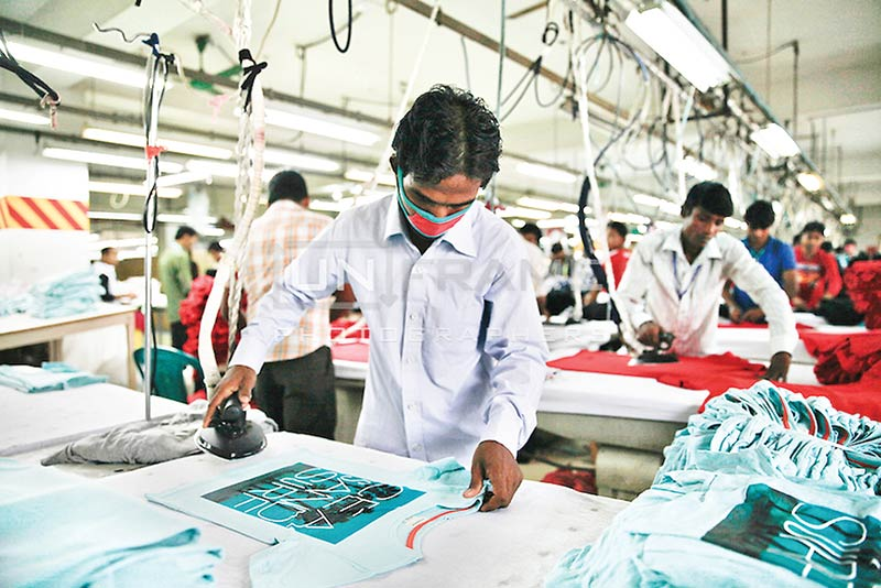 Male workers ironing clothes at a garment factory in Dhaka. However, women constitute more than 80 percent of employees in the country's garment sector.