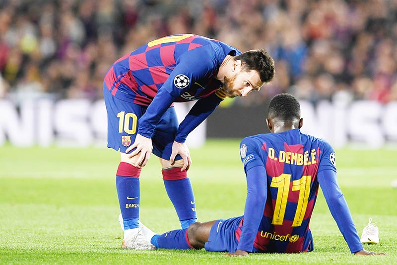 (FILES) In this file photo taken on November 27, 2019 Barcelona's French forward Ousmane Dembele (R) is conforted by Barcelona's Argentine forward Lionel Messi after an injury during the UEFA Champions League Group F football match between FC Barcelona and Borussia Dortmund at the Camp Nou stadium in Barcelona, on November 27, 2019.	photo: AFP