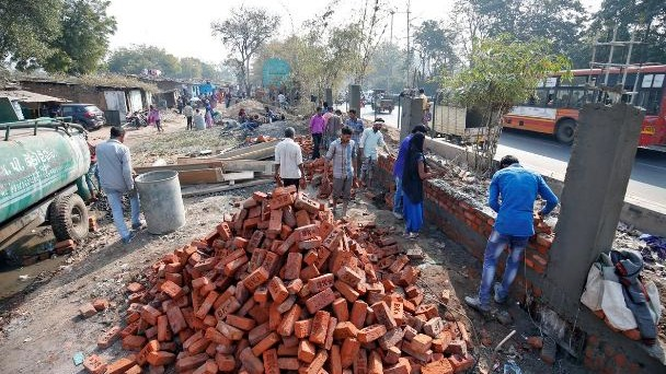 Construction workers build a wall along a slum area as part of a beautification drive along a route that US President Donald Trump and India's Prime Minister Narendra Modi will be taking during Trump's visit later this month, in Ahmedabad, India,on February 13, 2020. Photo: Reuters