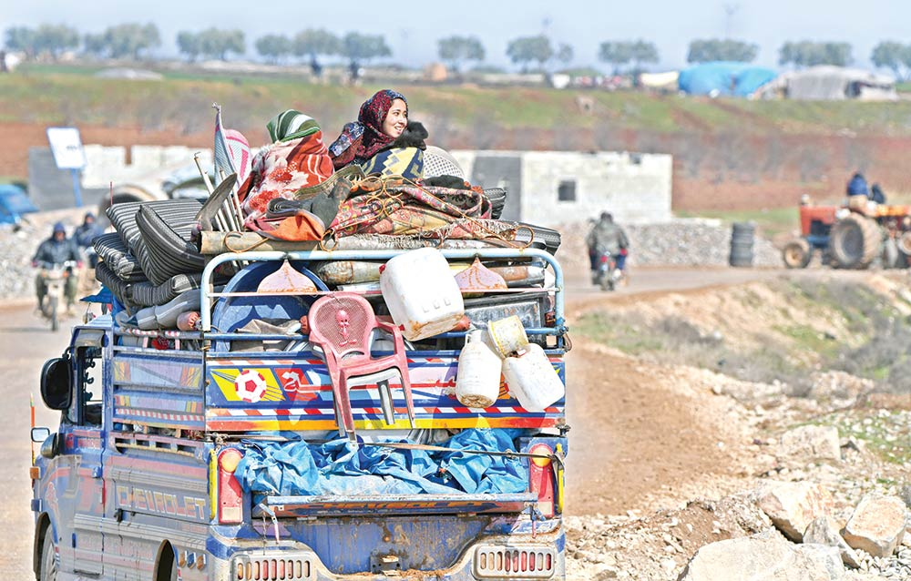 A displaced Syrian child rides a truck passing the rebel-held part of Syria's Aleppo province on February 14, fleeing from government forces advancing in the Idlib and Aleppo regions. Inset: A Turkish military convoy passes along the M4 motorway by the town of Ariha, south of Idlib.photo : AFP