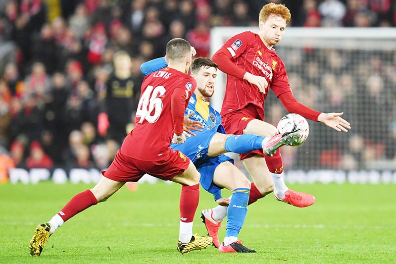Shrewsbury Town's English striker Callum Lang (C) vies with Liverpool's English defender Adam Lewis (L) and Liverpool's Dutch defender Sepp van den Berg (R) during the English FA Cup fourth round reply football match between Liverpool and Shrewsbury Town at Anfield in Liverpool, north west England on February 4, 2020.	photo: AFP