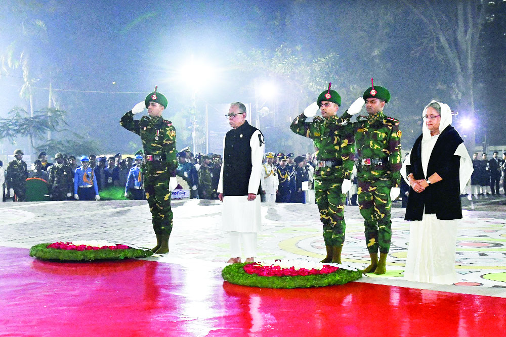 President Abdul Hamid and Prime Minister Sheikh Hasina stand in solemn silence after placing wreaths at the Central Shaheed Minar at one minute past midnight last night.PHOTO: PID