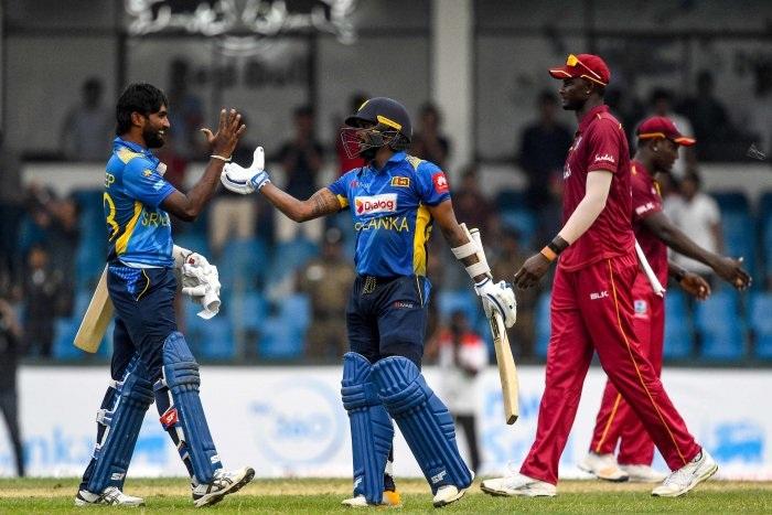 Sri Lanka's Wanindu Hasaranga (C) and Nuwan Pradeep (L) celebrate after Sri Lanka won by 1 wicket during the first one day international (ODI) cricket match between Sri Lanka and West Indies at the Sinhalese Sports Club (SSC) International Cricket Stadium in Colombo. (AFP Photo)