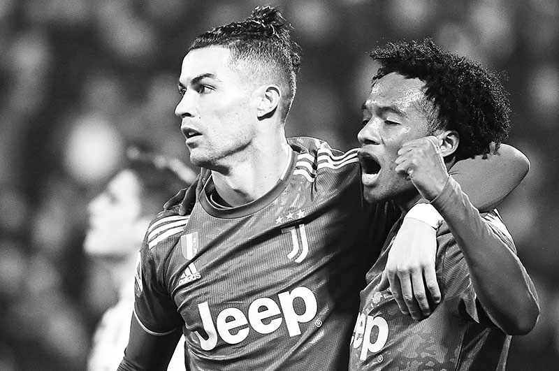 Juventus' Portuguese forward Cristiano Ronaldo (L) celebrates with Juventus' Colombian midfielder Juan Cuadrado after opening the scoring during the Italian Serie A football match SPAL vs Juventus on February 22, 2020 at the Paolo-Mazza stadium in Ferrara.photo: AFP