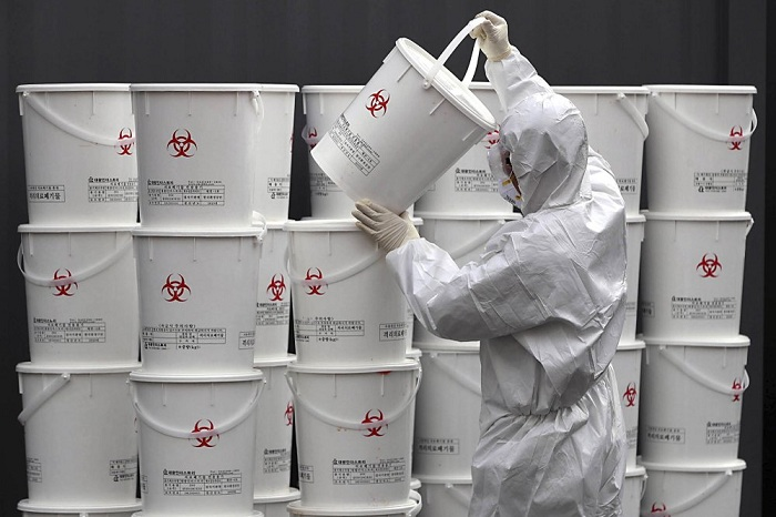 A worker in protective gear stacks plastic buckets containing medical waste from coronavirus patients at a medical center in Daegu, South Korea, Monday, Feb. 24, 2020. South Korea reported another large jump in new virus cases Monday a day after the the president called for