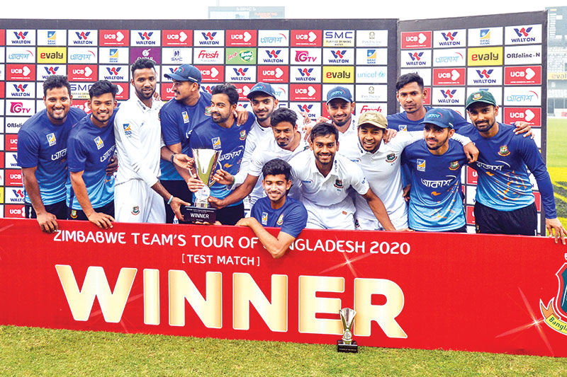 Bangladeshi cricketers pose for photos with the trophy following a presentation ceremony after winning the test match between Bangladesh and Zimbabwe during the fourth day at the Sher-e-Bangla National Cricket Stadium in Dhaka on February 25.	PHOTO: AFP
