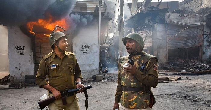 Security personnel stand near a burning shop in Gokulpuri, North East Delhi, on Wednesday, February 26. | PTI