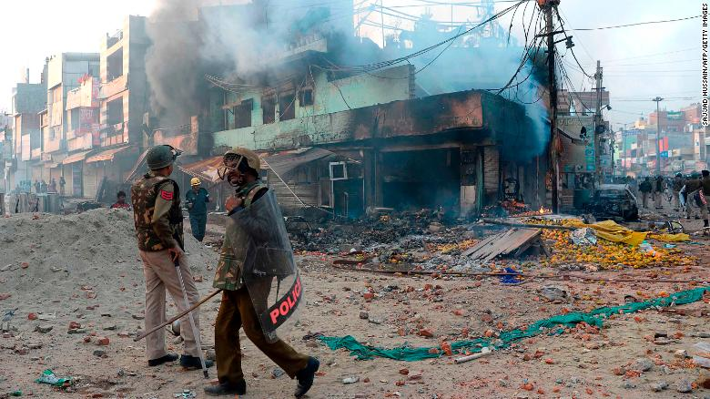 Policemen stand in front of burned shops in New Delhi following clashes over a new citizenship law on February 24.