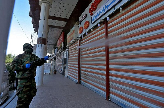 Iraqi health officials and Civil Defense staff wearing protective suits spray disinfectant as a precaution against the coronavirus in the closed shops, and hotels used by Iranian citizens in Najaf, Iraq. (AP)