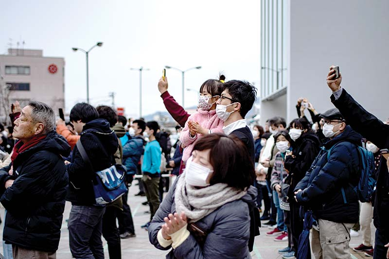 People wearing face masks watch the Tokyo 2020 Olympic flame displayed outside Miyako railway station, Iwate prefecture on March 22, 2020, after arriving from Greece.photo: AFP