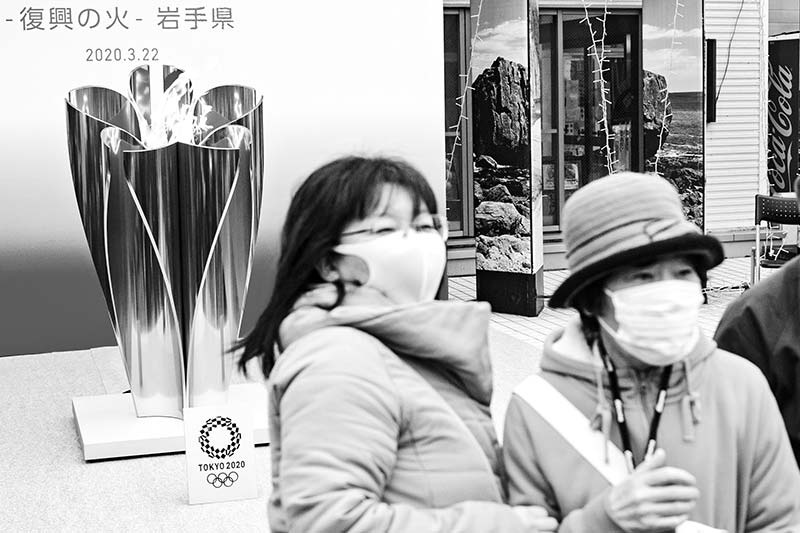 People wearing face masks take pictures in front of the Tokyo 2020 Olympic flame displayed outside the Miyako  railway station, Iwate prefecture on March 22, 2020, after arriving from Greece.photo: AFP