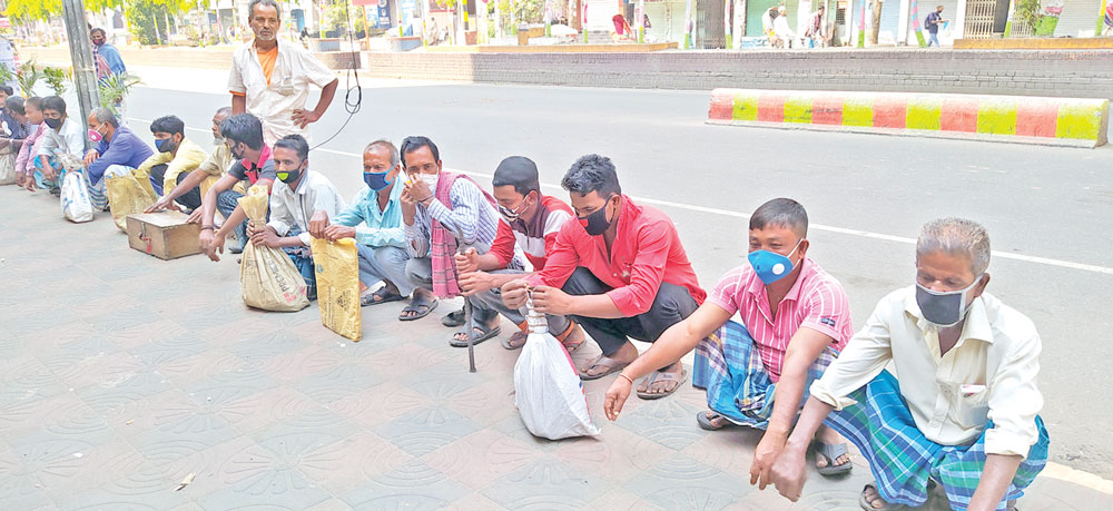 Photo shows construction labourers wait for customers throughout the day on the Bangabandhu Sarak in Narayanganj on Thursday, the first day of the 10-day lockdown in the country. photo  Observer