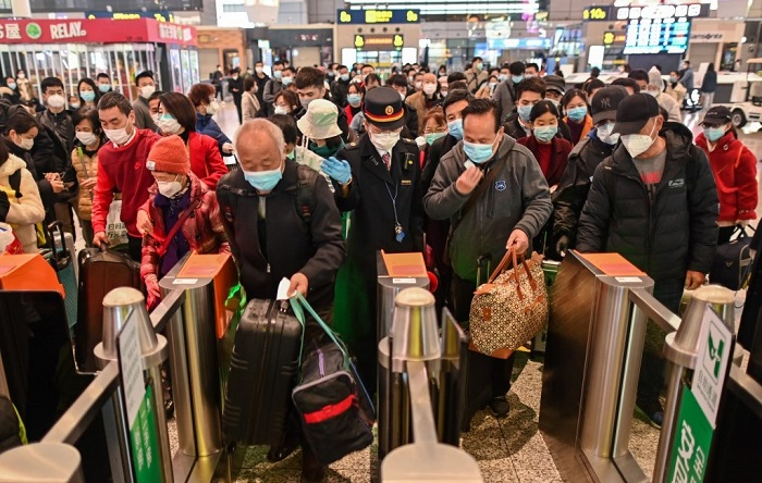 People wearing face masks as a preventive measure against the Covid-19 novel coronavirus walk to a train, one of the stops being Wuhan, at a station in Shanghai on March 28, 2020. Photo: AFP