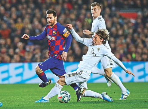 Barcelona talisman Lionel Messi (L) is hounded by Real Madrid player Luka Modric during their La Liga Clasico encounter at Camp Nou on Wednesday. Although Real pressed hard, the match ended in a draw. Photo: Reuters