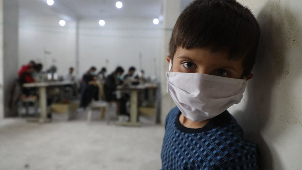 A child looks on as volunteers gather in a sewing workshop to make protective face-masks in the northeastern Syrian city of Idlib AFP/File