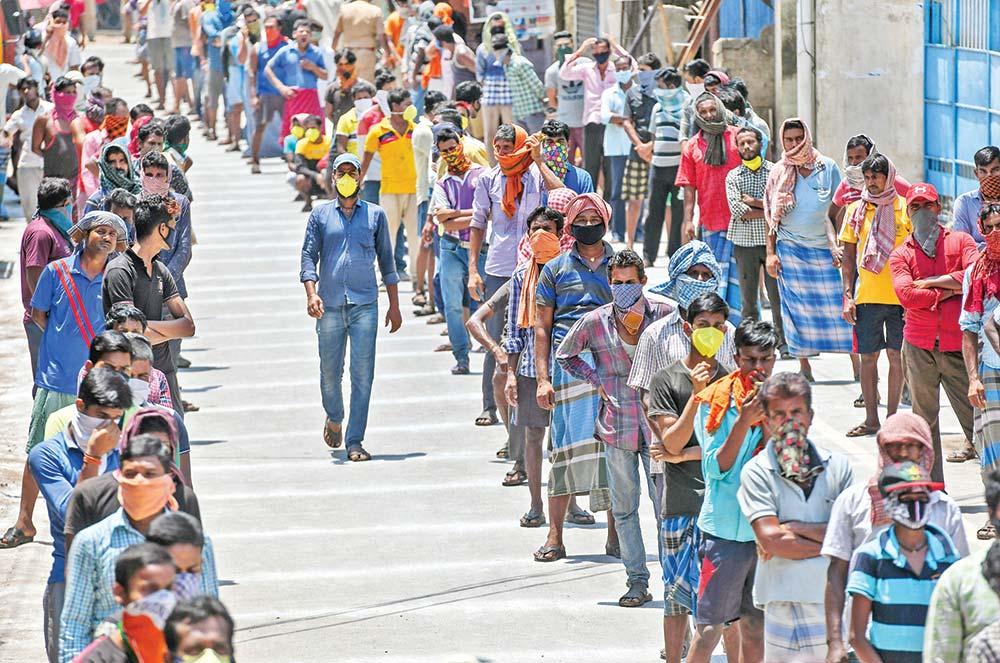 Migrant workers wait on marked areas on the ground to maintain social distancing as they queue to receive food packets at an industrial area during a government-imposed nationwide lockdown as a preventive measure against the COVID-19 coronavirus, in Chennai on April 1.photo : AFP