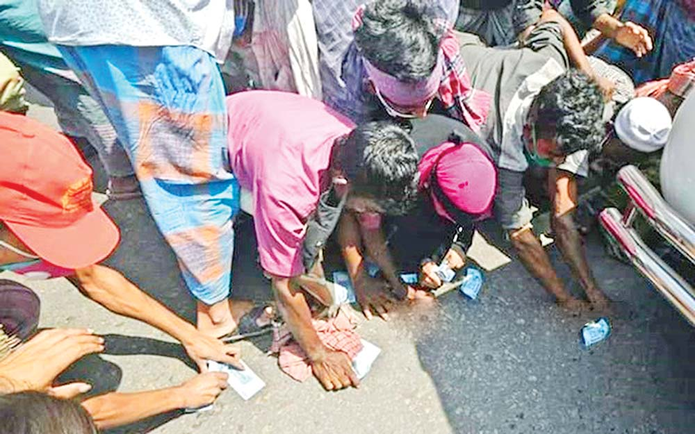 Destitute people jostling to get money tossed by the chief executive officer (CEO) of Dhaka South City Corporation in Science Laboratory area on Thursday.photo : bdnews24.com