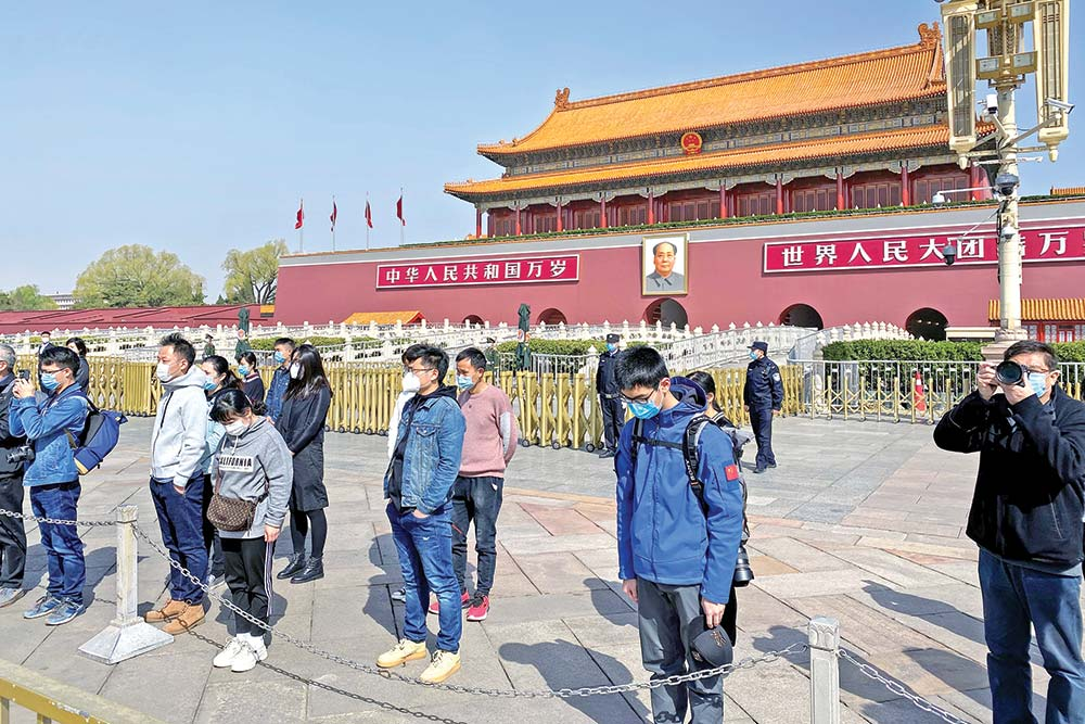 People bow in front of Tiananmen Gate in Beijing during a three minute national memorial to commemorate people who died in the COVID-19 coronavirus outbreak, on April 4. China came to a standstill to mourn patients and medical staff killed by the coronavirus, with the world's most populous country observing a nationwide three-minute silence.photo : AFP