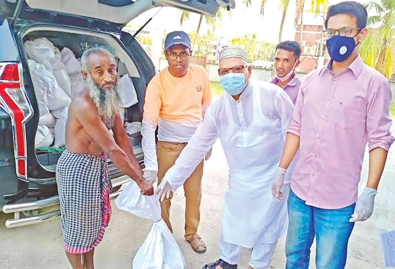 Char Fasson Upazila Chairman Alhaz Md Joynal Abedin Akhon and UNO Md Ruhul Amin distributing food items to poor people who became workless for coronavirus outbreak on Upazila Parishad premises in Bhola on Wednesday.photo: observer