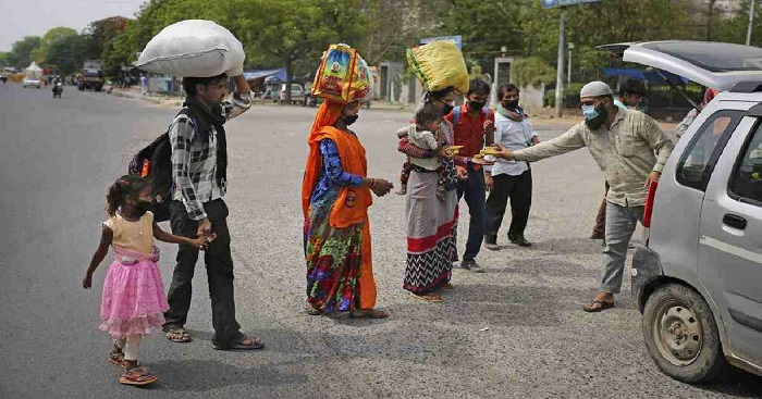 A family of migrant workers receive bananas and biscuits from a man as they walk along a highway hoping to reach their home, hundreds of miles away, during a nationwide lockdown to curb the spread of new coronavirus in New Delhi, India. AP File Photo