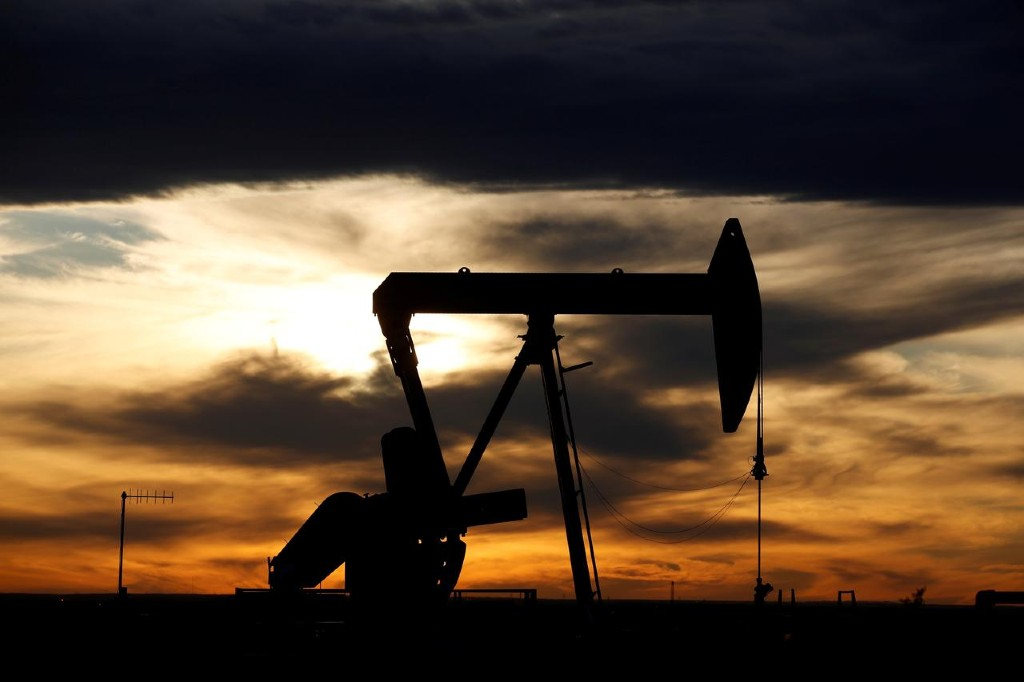 The sun sets behind a crude oil pump jack on a drill pad in the Permian Basin in Loving County, Texas, US. Photo: Reuters
