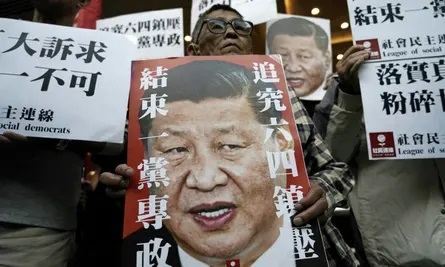Pro-democracy activists hold up placards of Chinese President Xi Jinping with slogans including 'End one party state' at a ferry terminal in Hong Kong. Photograph: Kin Cheung/AP