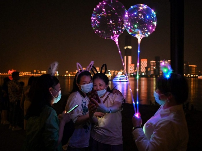 Women wearing face masks take a selfie in Hankou Park in Wuhan, in China's central Hubei province on May 22, 2020.HECTOR RETAMAL / AFP via Getty Images