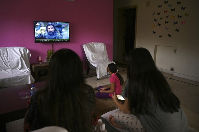 In this picture taken on May 9, 2020, a family watches a Turkish drama series 'Dirilis: Ertugrul' telecasted on Pakistan's state-run channel PTV Home during the holy month of Ramadan in Islamabad. (AFP/Aamir Qureshi)